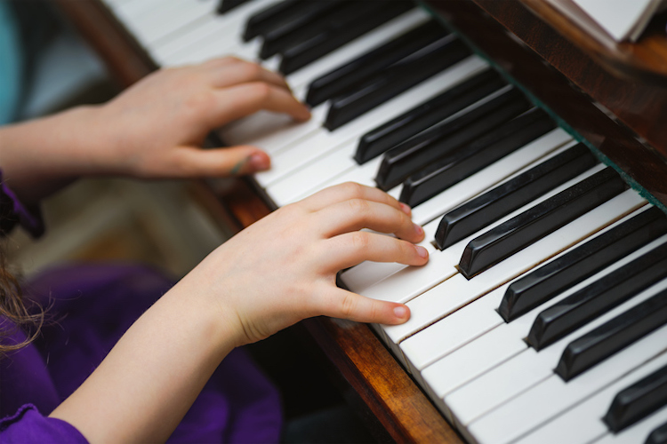 kids hands on a white piano key. Playing music